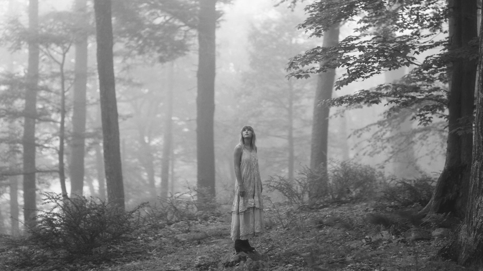 Taylor Swift standing in a forest